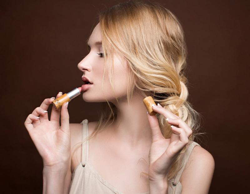 blond girl putting on lipstick