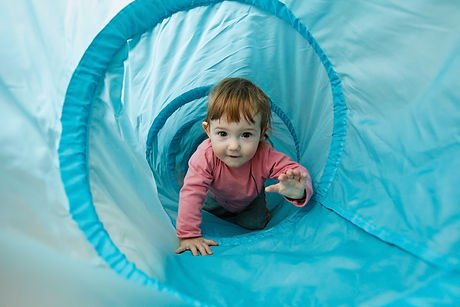 Small toddler playing in a tunnel tube, crawling through it and having fun.jpg
