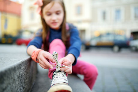 Cute little girl learning to tie shoelaces outdoors on summer day_
