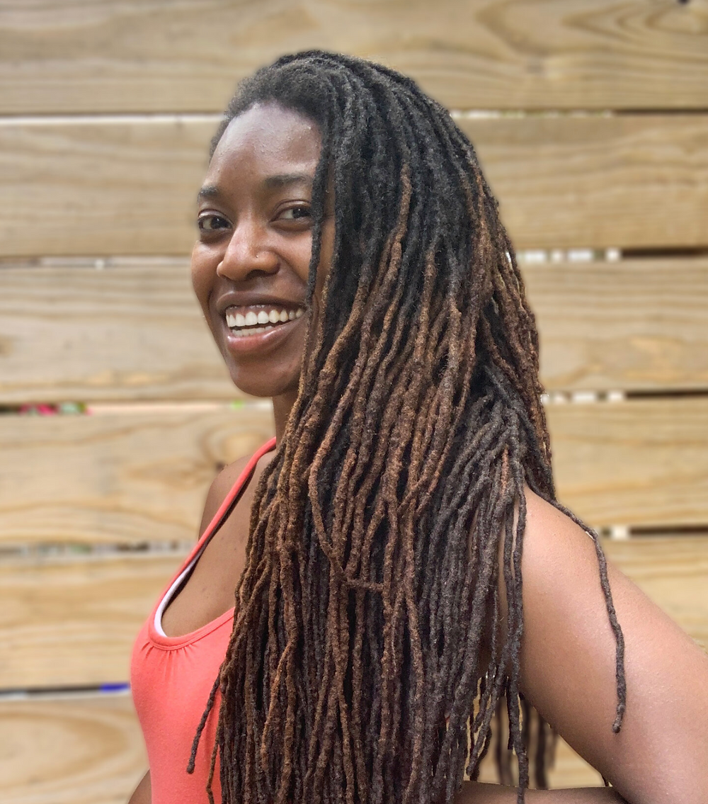 A young Black woman with long dreadlocks and seemingly perfect white teeth is smiling at the camera. She wears a salmon colored tank top.
