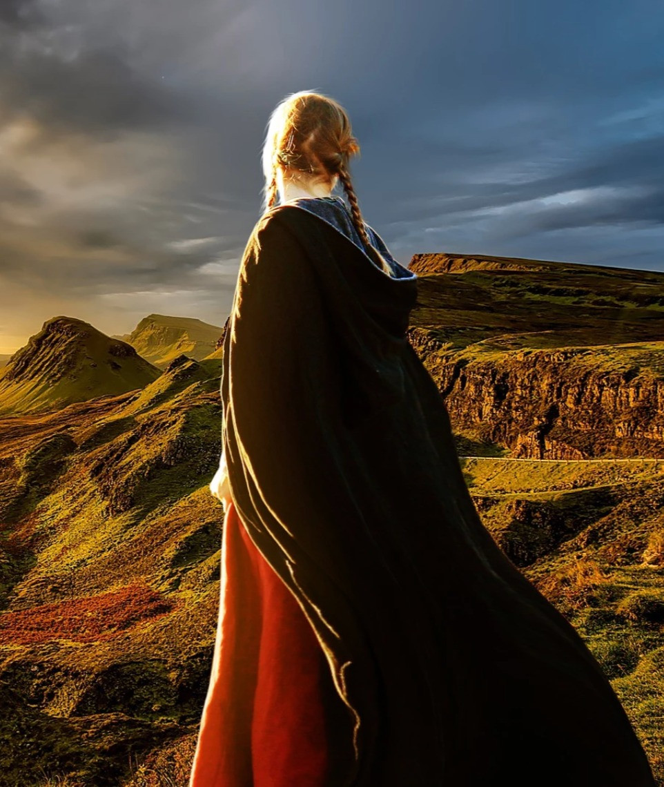 a young white woman with blonde hair and dressed in a flowing cape is looking off into the mountains