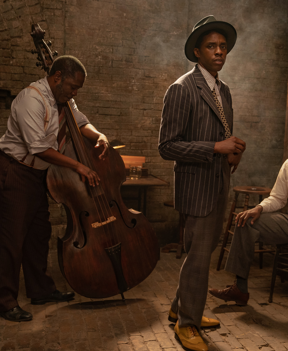 2 men dressed in 1920's attire stand in a dark room. One looks at the camera while the other plays a viola.