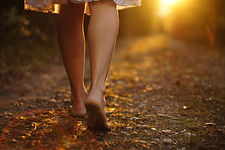 Young female legs walking towards the su