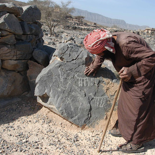 A man part of the Al Shuhuh tribe with an ancient stone carving