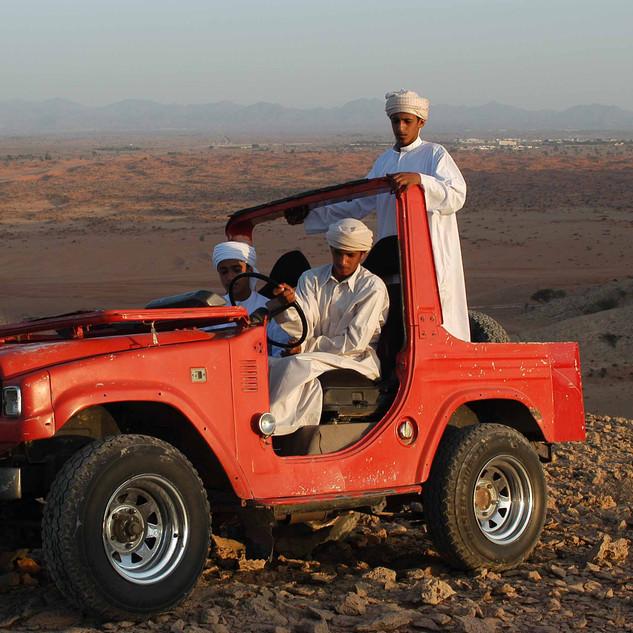 Emirati men driving an SUV in the desert