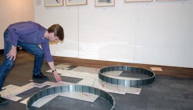 Exhibition view, Raymond Prucher installing his work