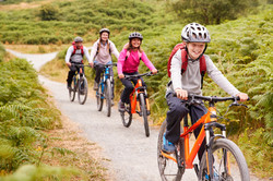 Pre-teen boy riding mountain bike with h