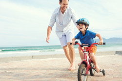 Father and son learning to ride a bicycl