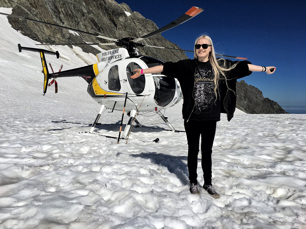 Female travel blogger in front of helicopter atop either Franz Josef or Fox glacier