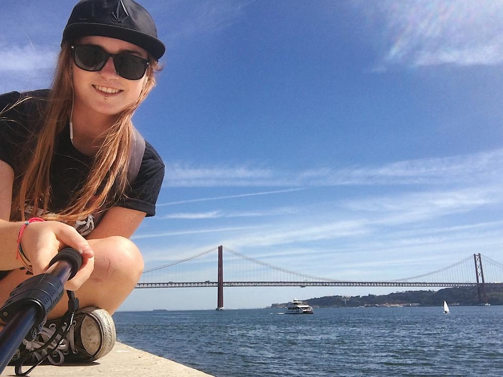 Female travel blogger and Ponte de 25 abril, Lisbon