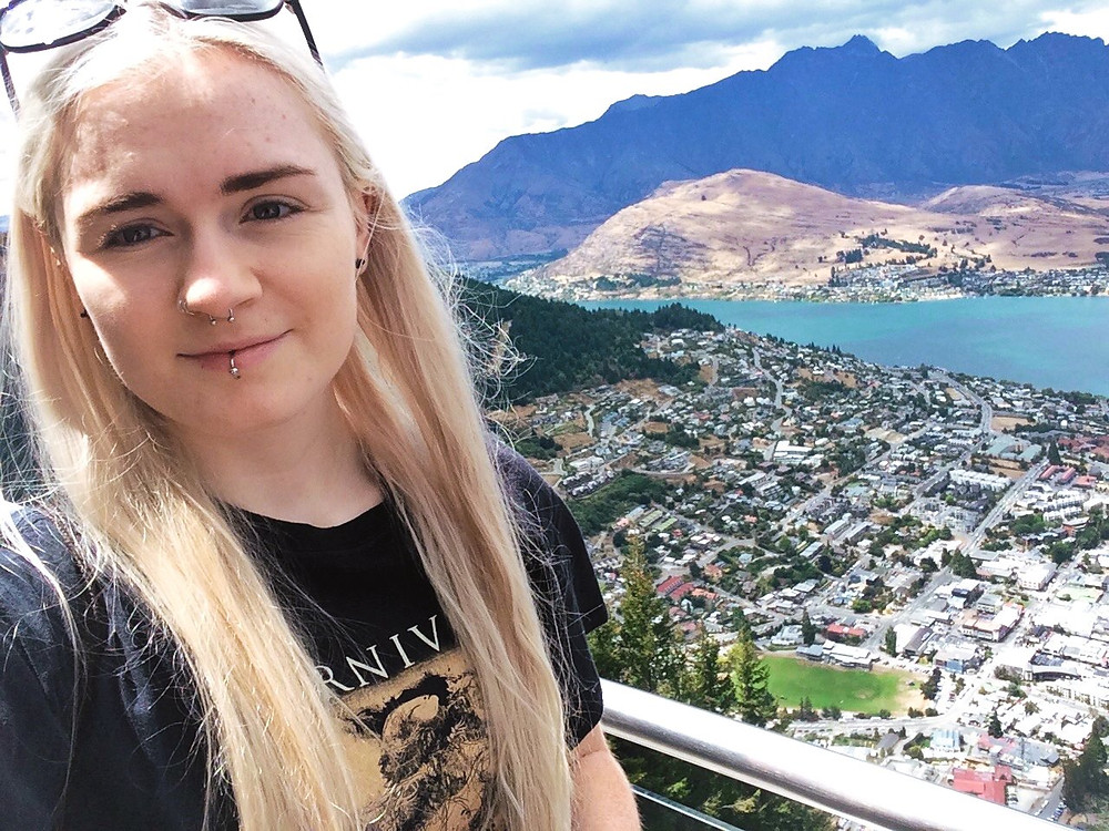 Female travel blogger in front of a view of Queenstown