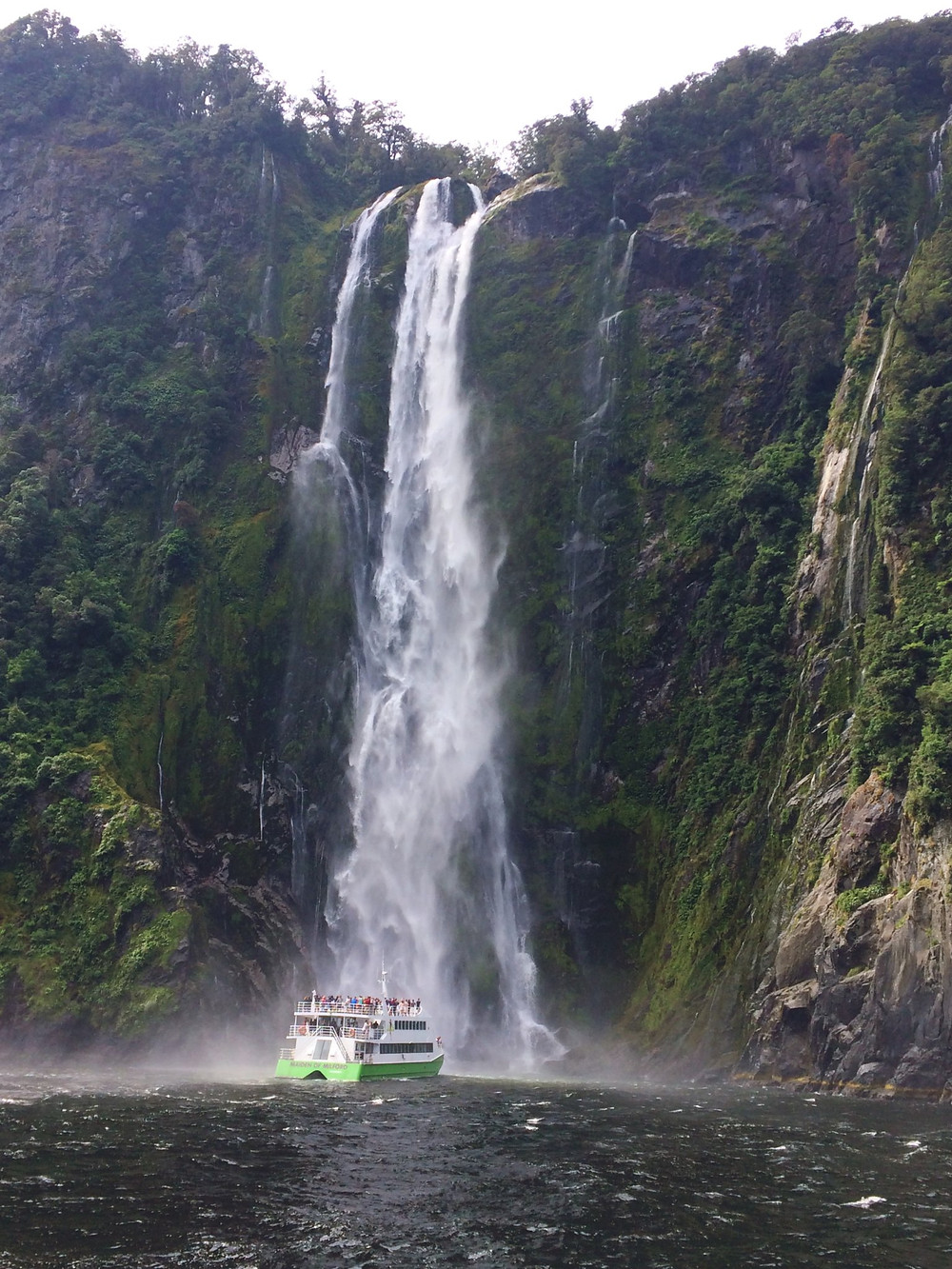 A cruise ship dips under Stirling Falls at Milford Sound