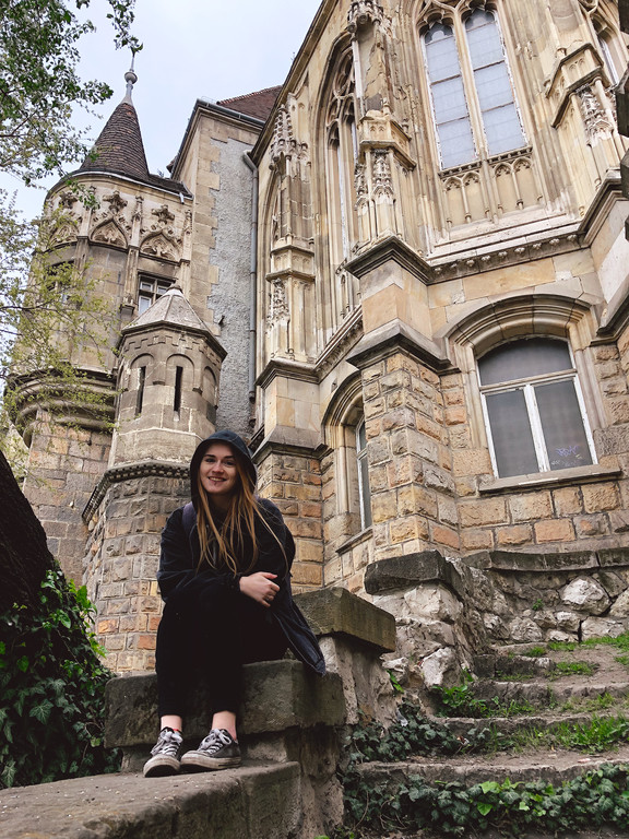 Female travel blogger at Vajdahunyad Castle, Budapest