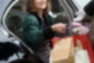 Woman handing shopping bags to valet