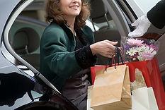 Donna che passa borse della spesa a serv