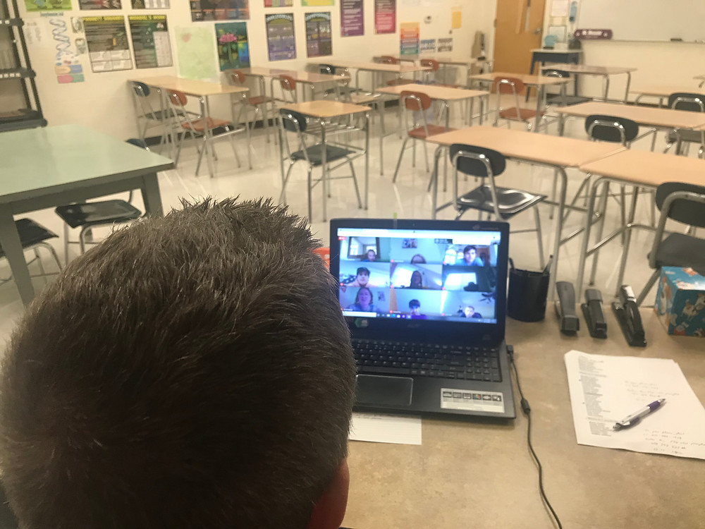 Middle School Science Teacher Jason Messier teaches to a full virtual classroom while his actual classroom remains empty of students.