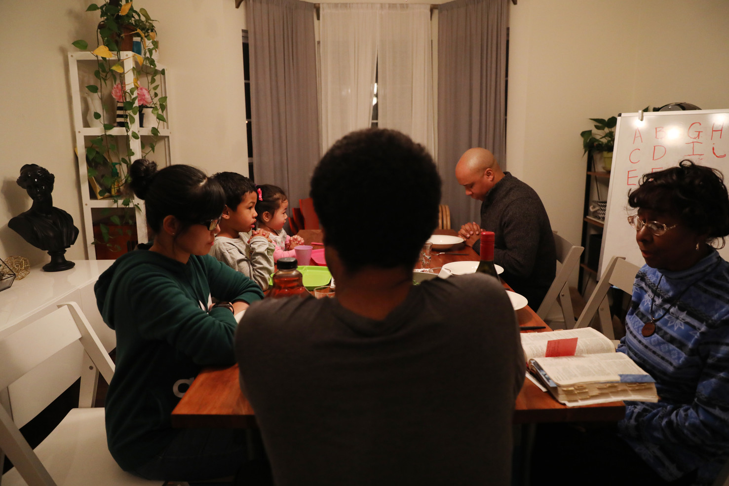 The two-generation family pray before Thanksgiving dinner on Thursday, November 28, 2019 in Columbia, Missouri. Instead of following all formal religious behaviors, Yan and her husband focus more on mentally religious belief. Sometimes, Arthur reminds to have a pray before dinners while parents forget.   Yan Guo Fulcher and Brandon Fulcher decided to get married and have a faithful Christian family in 2007. After their son and daughter, Arthur, 6, and Jane, 3, was born, they bring children to be familiar with Christianity by going to church every Sunday, attending church's events and celebrating every religious holiday, but at the same time, give more spaces in choosing religions. Love, respect, and open-mindness are Yan and her husband's principles of education inspired by the Bible. They give children endless love, and respect and accept children's decisions while growing up.