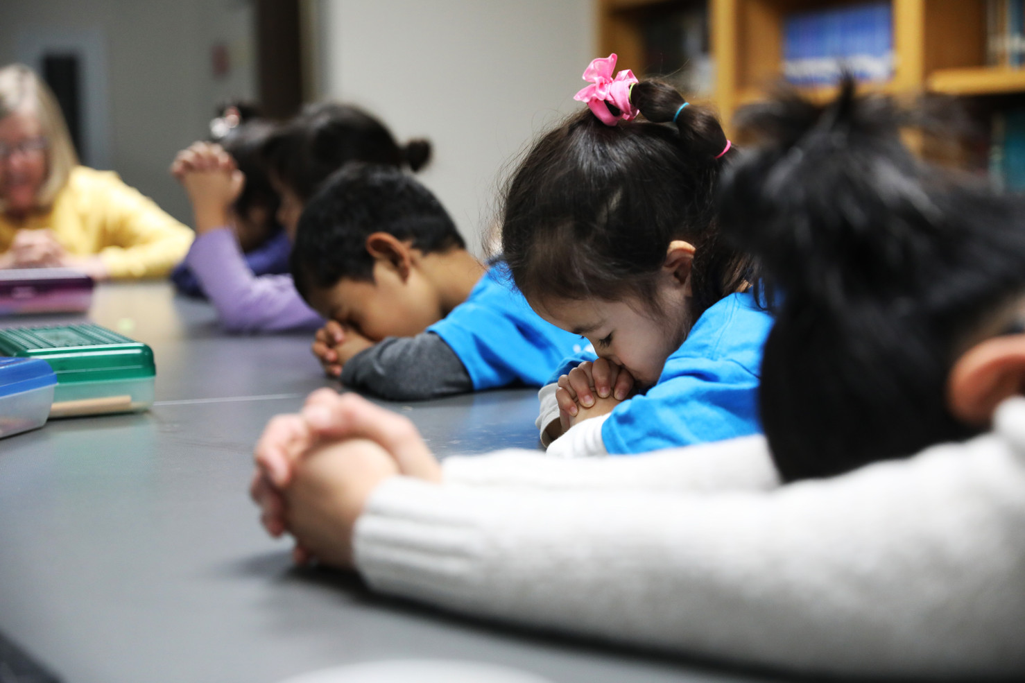 Arthur, Jane, and Yan pray before class in Children's Sunday School beginning on Sunday, November 17, 2019 in Children's Sunday School in International Community Church, Columbia, Missouri. In Children's Sunday School, children learn the Bible by singing religious songs, painting, and making with elements of religions.
