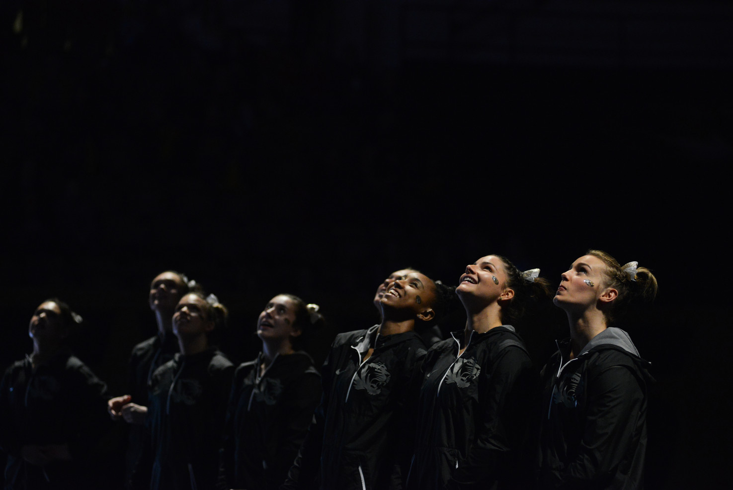 Members of the Missouri gymnastics team look up at the JumboTron on Friday, March 15, 2019 at the Hearnes Center, Columbia, Missouri. At the beginning of the meet, a ceremony honored six senior gymnasts.