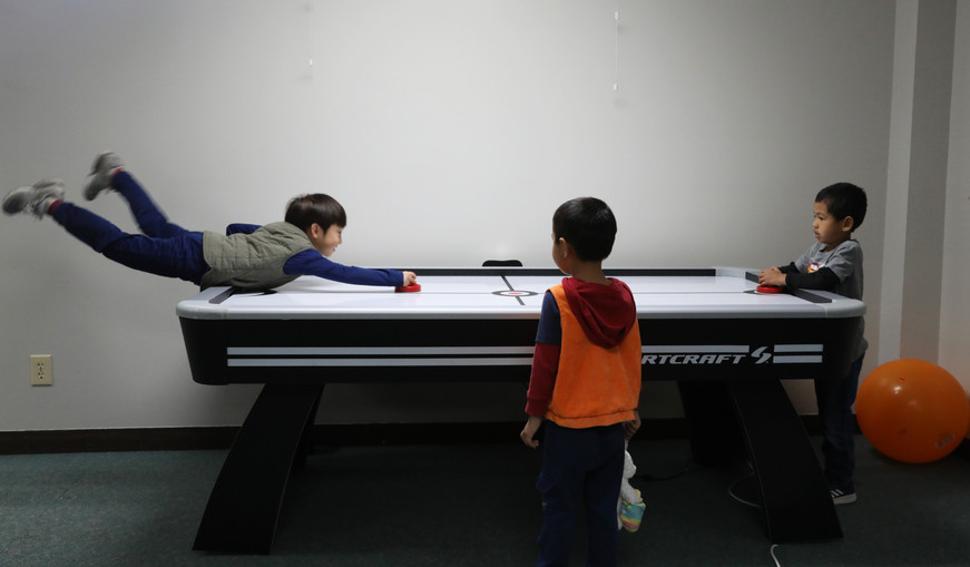 Arthur, right, plays air hockey with his church friends on Sunday, November 10, 2019 in Children's Sunday School in International Community Church, Columbia, Missouri. Usually, children stand on a line and wait for playing the game after Sunday Church finishing.