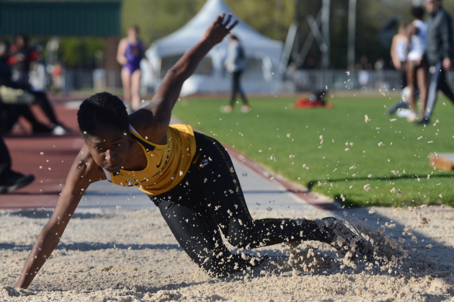 Sand flies through the air as Missouri's Kalescia Thomas lands in the pit during the long jump at the Tom Botts Invitational on Friday, April 20, 2019 at Andrey J. Walton Stadium, Columbia, Missouri. Missouri's men's and women's track and field teams hosted the first day of the Tom Botts Invitational on Friday at Audrey J. Walton Stadium. Missouri athletes participated in many events, including the hammer throw, long jump, javelin throw, 3,000-meter steeplechase, 1,500-meter run and 5,000-meter run.