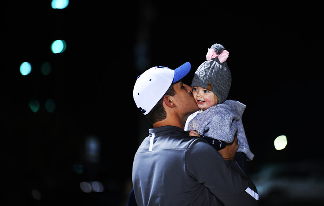 Wes Hamilton, assistant coach of Tolton's football team, kisses his daughter Joella Hamilton during a game against Helias on Friday at Tolton Catholic High School. Hamilton's wife, Audrey, drove Joella from Fulton to visit Wes.