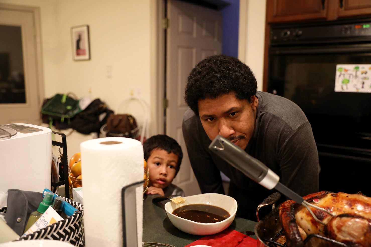 Arthur Fulcher and Brandon look at a meat cooking thermometer inserted into Thanksgiving turkey on Thursday, November 28, 2019 in Columbia, Missouri. Brandon's mother and brother, Joanne and Bryan, come to their house and celebrate Thanksgiving which is the most important holiday for them.