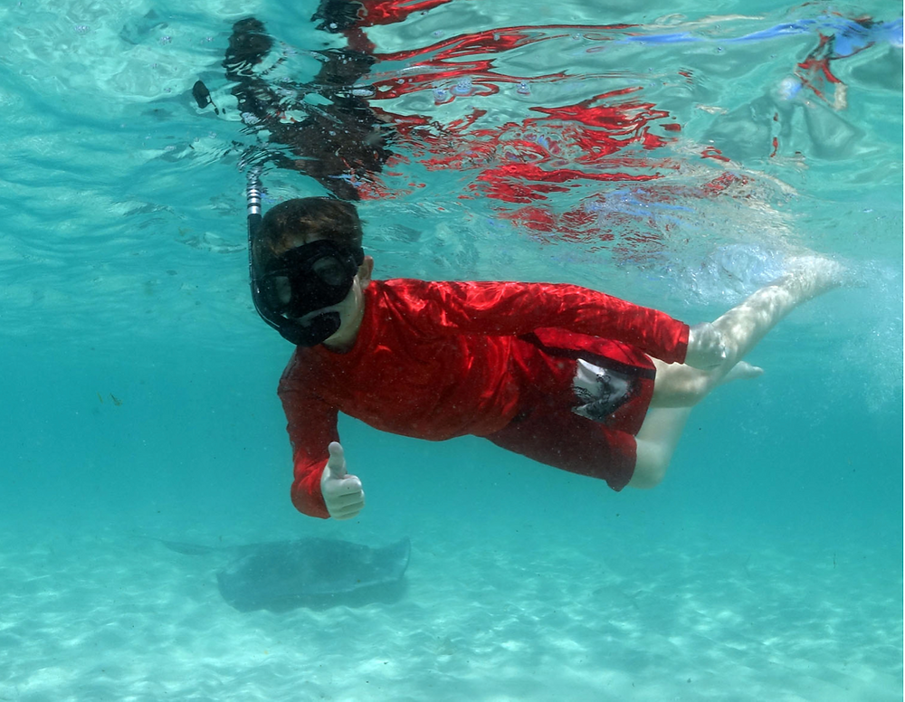 Christopher snorkeling with stingrays Credit: Duncan Brake