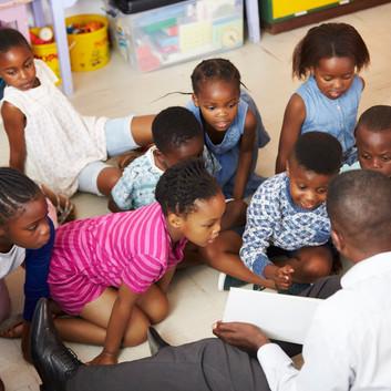 teacher-reading-kids-a-book-in-an-elemen