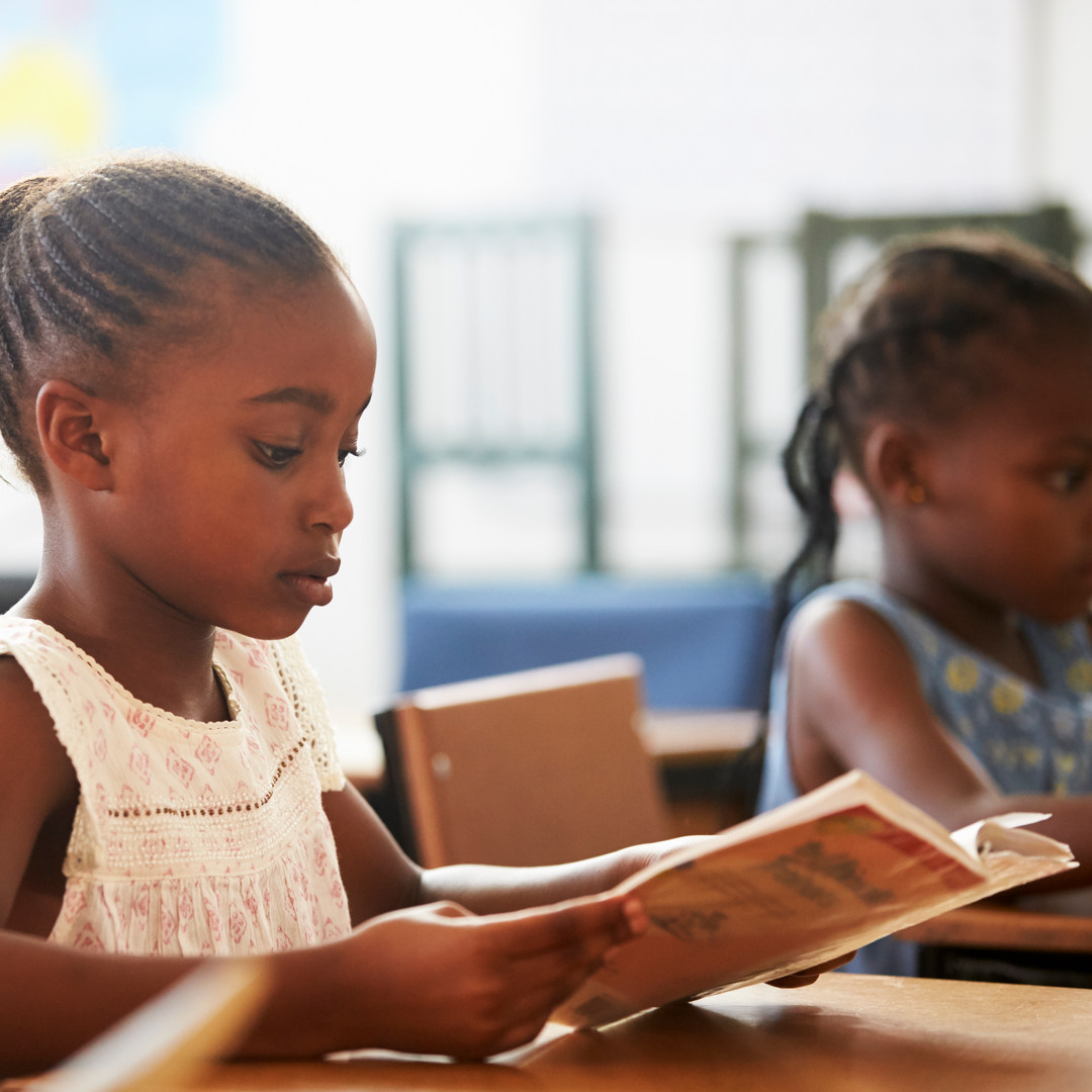 girl-holding-book-and-reading-in-an-elem