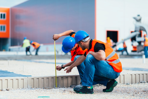 Construction workers measuring a foundation with a tape measure