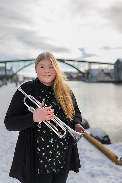 Bildet viser Mari som står på kaien i Haugesund med en trompet i hånden.