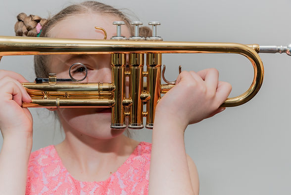 A young girl holds a trumpet in front of