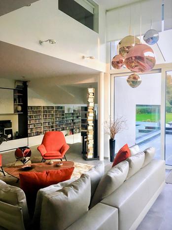 Intérieur contemporain: salon et bibliothèque avec espace ouvert sur mezzanine