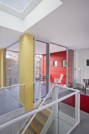 Réhausse contemporain à Jette: intérieur lumineu mur rouge et grande vitres
