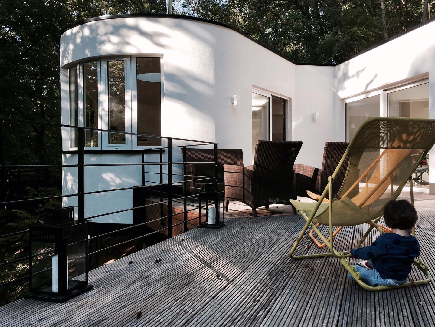 Maison contemporaine à Wavre: enfant sur terrasse en bois toit plat