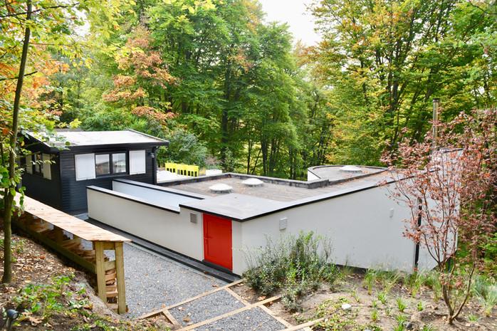 Maison écologique à Wavre: semi-enterrée avec porte rouge et toit plat