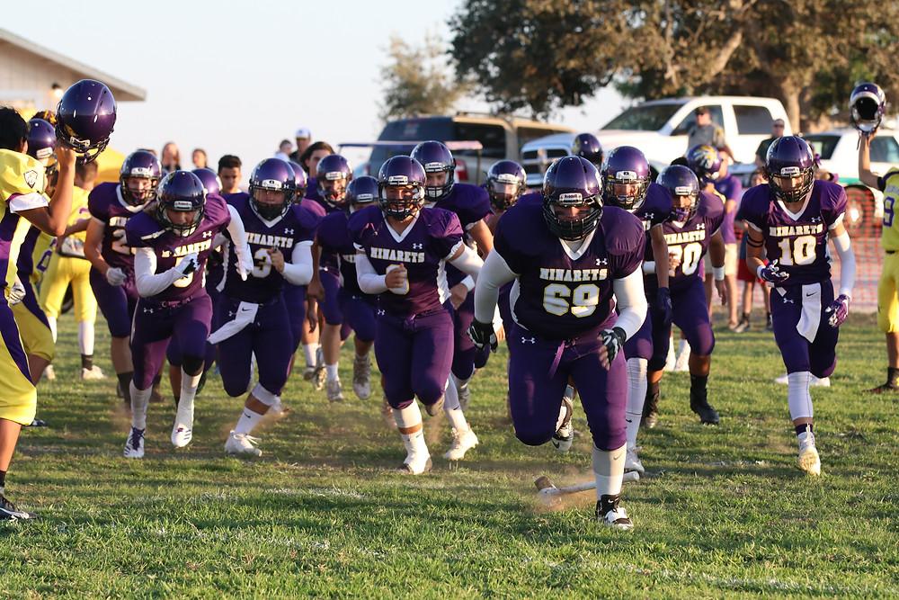 Varsity team runs in for their game against Orosi.