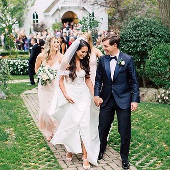 Bride, groom, and wedding party walking outside following the wedding. Groom is wearing a custom tuxedo, handmade in Toronto by MICHEL'S BESPOKE.