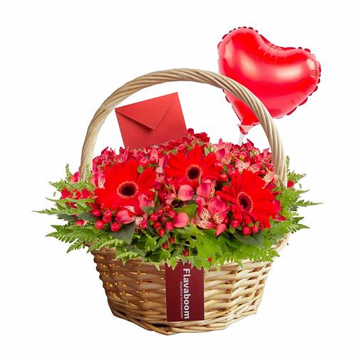 Arreglo floral en cesto de mimbre con globo de corazón y flores variadas