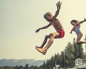 Kids jumping off dock in lake