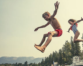Kids jumping off dock in lake