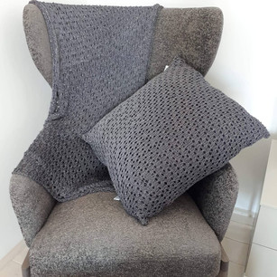 Hand-knitted throw and pillow in lurex yarn.
