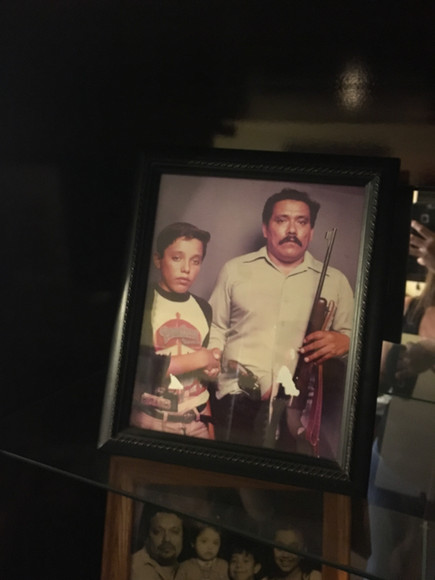 An elegant oak and glass stand in the living room holds a photo of Olivia's grandfather, Cruz Barrios, and his son Valentín. This photo was taken in 1984 in East Los Angeles.