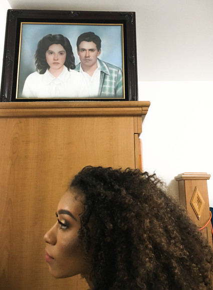 She looks in the mirror in her grandmother's bedroom. Above her, an oil painting of her grandparents.