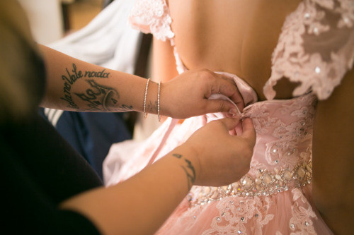 """Cynthia, Olivia's cousin, fastens the laces on her corset. On her arm, a tattoo that reads """"La vida no vale nada""""(Life is worth nothing), lyrics from a popular Mexican song by the same title. ."""