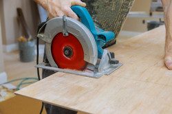hands-worker-cut-plywood-with-circular-s