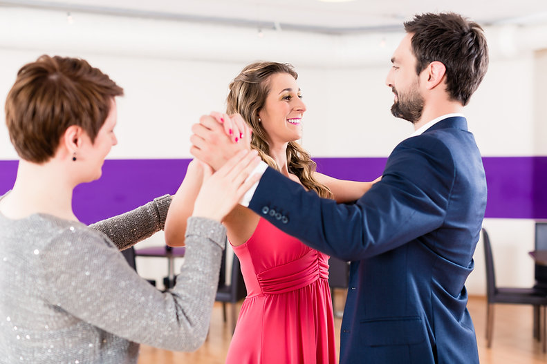 Instructor in dance school with couple o