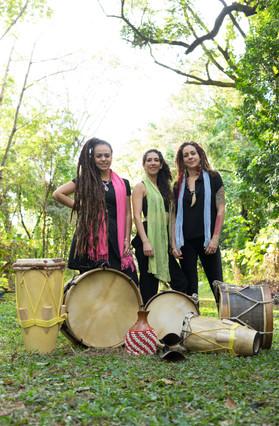 As mulheres estão de pé, e lado a lado, atrás de diferentes instrumentos de percussão. Além dos tambores mineiros, estão dois atabaques, que são tambores mais altos e estreitos, e um xequerê, composto por uma cabaça grande, envolta em uma rede com contas brancas e vermelhas.