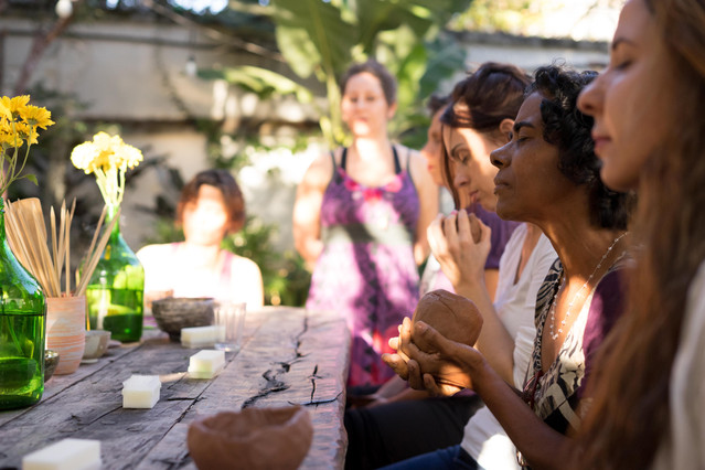 Sentadas ao ar livre, quatro mulheres tocam peças de cerâmica, com os olhos fechados. À frente delas, há uma mesa de madeira rústica, sobre a qual há garrafas de vidro verde com flores e um pote de cerâmica com varetas de madeira. No fundo desfocado, estão Flávia de pé e uma mulher sentada, ambas iluminadas pelo sol.